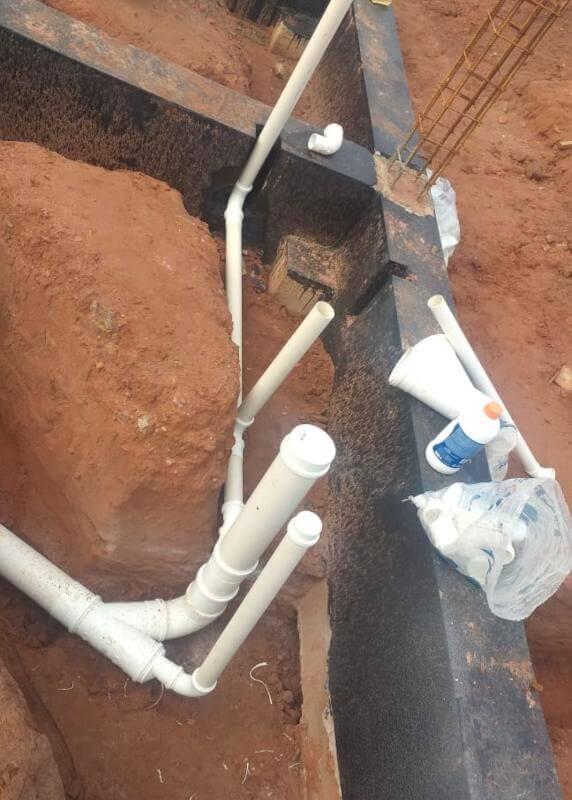 Montagem de tubulações subterrâneas em obra residencial